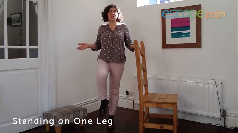 Image of a woman doing an exercise in her living room using a chair as a prop